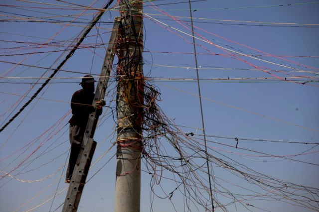 A man tries to connect his store with electricity from the main electricity pole at the Zaatari Refugee Camp, in Mafraq, Jordan, Tuesday April 22, 2014. An estimated 104,494 refugees reside in the sprawling Zaatari refugee camp, according to the United Nations High Commissioner for Refugees (UNHCR), with the majority of the population coming from the Daara Governorate in southwest Syria. (AP Photo/Mohammad Hannon)
